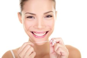 Dental flush - woman flossing teeth smiling